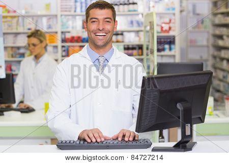 Happy pharmacist using computer at the hospital pharmacy