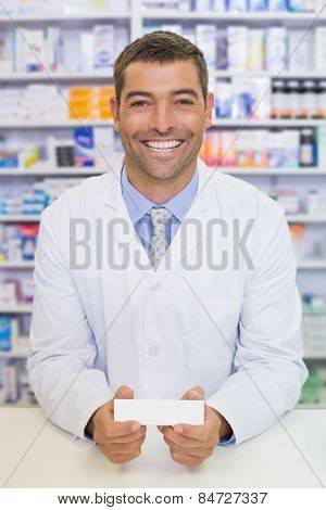 Handsome pharmacist holding medicine box at the hospital pharmacy