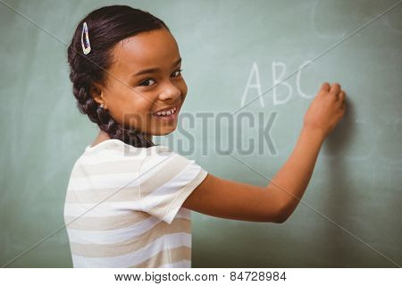 Portrait of cute little girl writing ABC on blackboard in the classroom