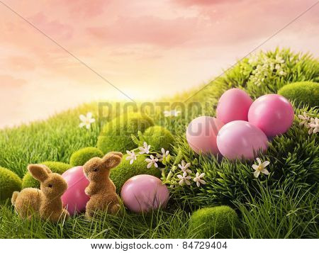 Pink easter eggs and rabbit on green grass