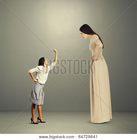 small woman screaming and showing fist to big angry woman over dark background
