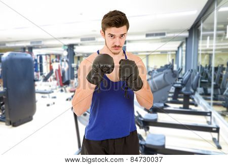 Man with black boxing gloves at the gim
