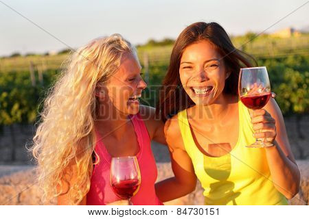 Happy women friends drinking red wine laughing in vineyard in summer. Young laughing girlfriends drinking rose wine from glass outside.