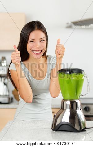 Vegetable smoothie woman happy thumbs up blending green smoothies with blender home in kitchen. Healthy eating lifestyle concept portrait of beautiful young woman preparing drink with spinach etc