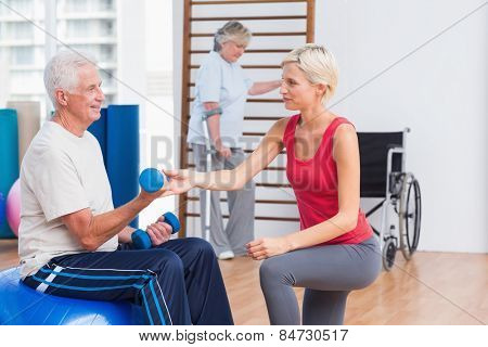 Female trainer assisting senior man in exercising with dumbbells while woman using crutches in background at gym