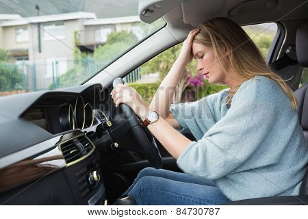 Worried woman sitting in drivers seat in her car