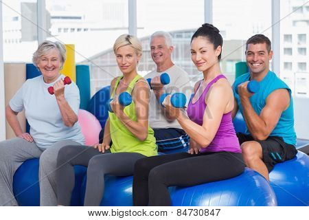 Portrait of people on exercise balls while working out with dumbbells in gym class