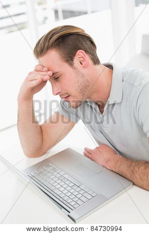 Anxious businessman working with laptop in his office