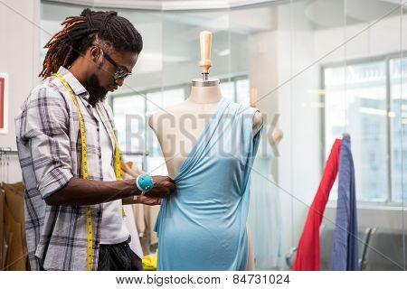 Side view of male fashion designer and mannequin