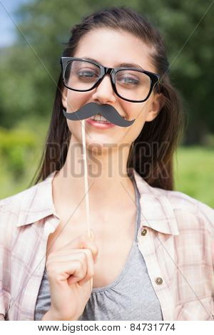 Pretty brunette smiling at camera with fake mustache on a sunny day