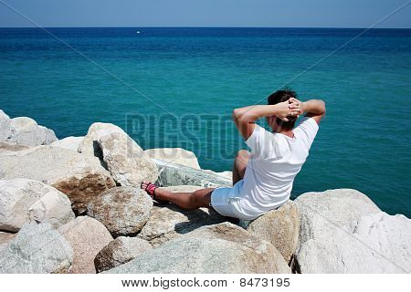 A Man Sitting On Cliffs And Enjoys The Aegean Sea View