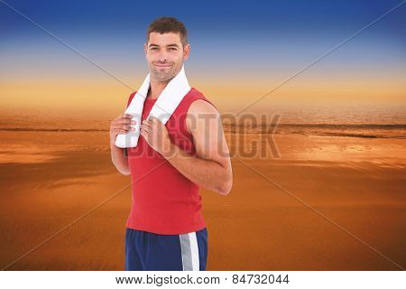 Fit man smiling at camera against hazy blue sky