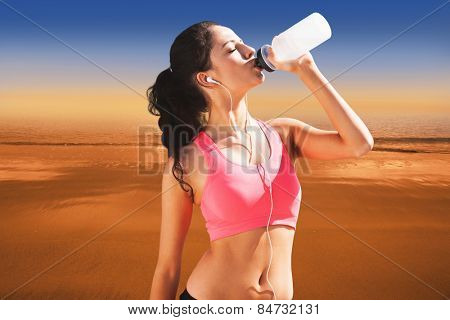 Beautiful healthy woman drinking water against hazy blue sky