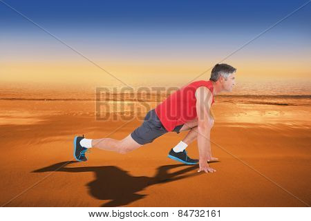 Fit man stretching his legs against hazy blue sky