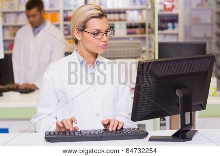Concentrate pharmacist using computer at the hospital pharmacy