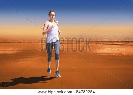 Focused fit blonde jogging against hazy blue sky