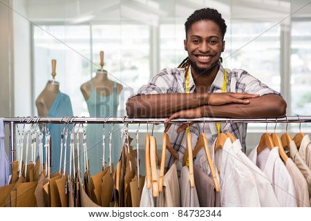 Portrait of male fashion designer leaning on rack of clothes