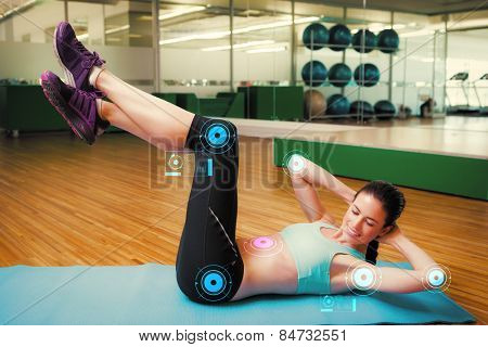 Fit brunette doing sit ups in fitness studio against fitness interface