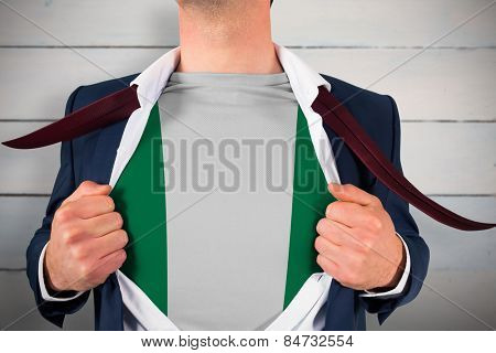 Businessman opening shirt to reveal nigeria flag against painted blue wooden planks