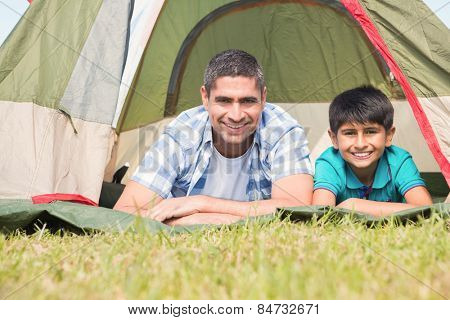 Father and son lying beside their tent on a sunny day