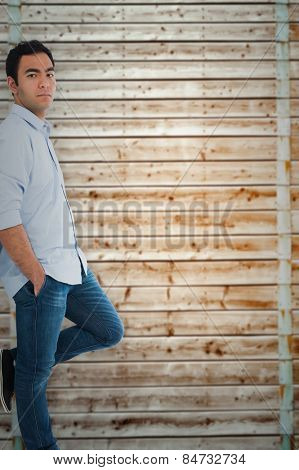 Unsmiling casual man standing against wooden background in pale wood