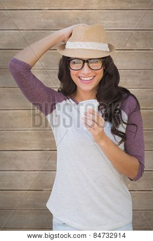 Brunette with disposable cup against wooden planks