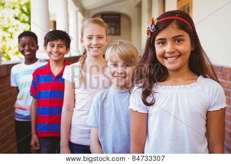 Portrait of smiling little school kids in school corridor