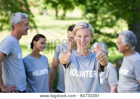 Happy volunteer blonde with thumbs up on a sunny day