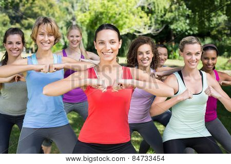 Fitness group squatting in park on a sunny day