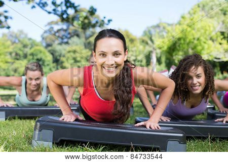 Fitness group using steps in park on a sunny day