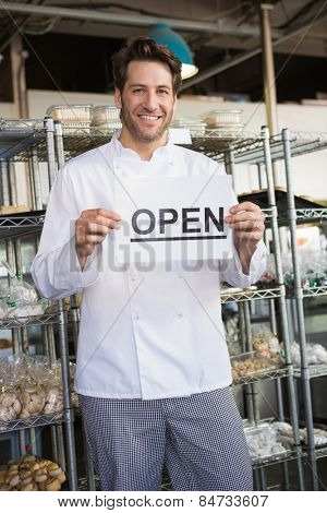 Portrait of a smiling baker holding open sign at the bakery