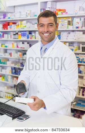 Handsome pharmacist scanning medicine box at the hospital pharmacy