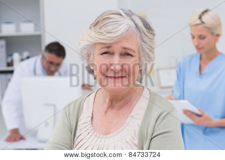 Portrait of unhappy senior patient with doctor and nurse working in background at clinic