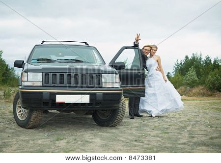 Happy Newly-married Couple Says Goodbye Near Car