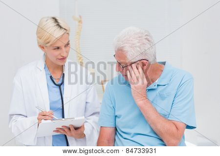 Female doctor explaining prescription to senior male patient in clinic