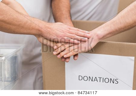 Volunteer team holding hands on a box of donations in a large warehouse