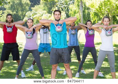 Fitness group working out in park with kettle bells on a sunny day