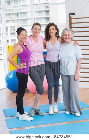 Full length portrait of happy women standing arms around in gym