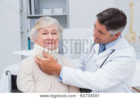 Male doctor examining senior patient wearing neck brace in clinic