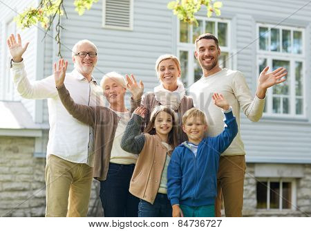 gesture, happiness, generation, home and people concept - happy family waving hands in front of house outdoors