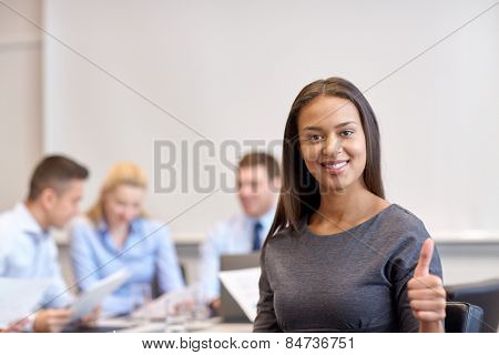 business, people and teamwork concept - smiling businesswoman showing thumbs up with group of businesspeople meeting in office