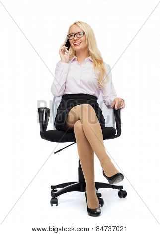business, style and people concept - smiling businesswoman, student or secretary sitting in office chair and calling on smartphone over white background