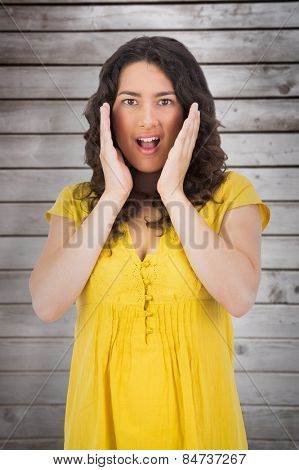 Disgusted casual young woman posing against wooden planks