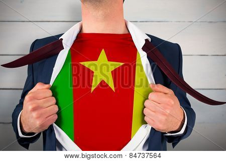 Businessman opening shirt to reveal cameroon flag against painted blue wooden planks