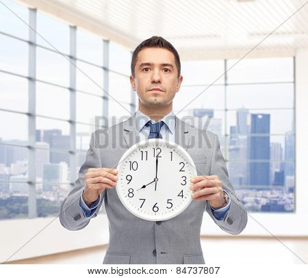 business, people, time management and office concept - businessman in suit holding clock showing 8 o'clock up over city office window background