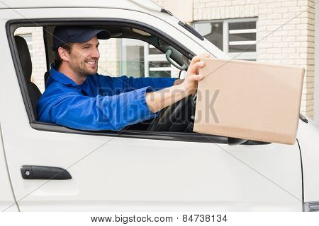 Delivery driver offering parcel from his van outside the warehouse