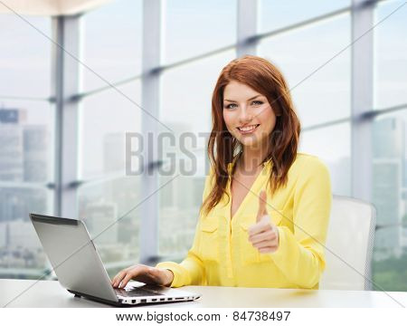 people, business and technology concept - smiling young woman with laptop computer showing thumbs up and sitting at table over office window background