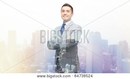 business, people and office concept - happy smiling businessman in suit over city background with double exposure