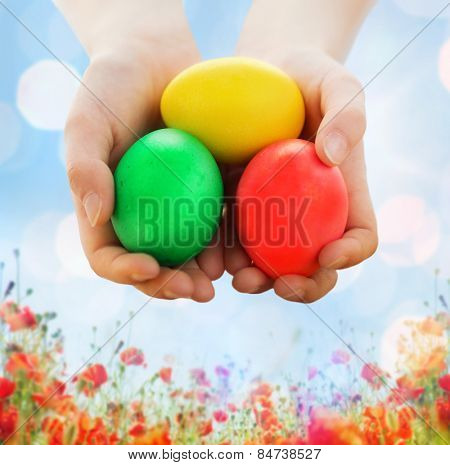 easter, holiday and child concept - close up of kid hands holding colored eggs over blue sky and poppy field background