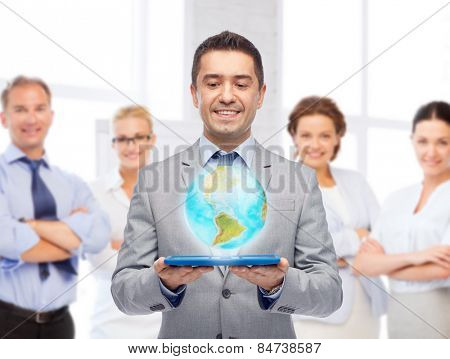 global business, people and technology concept - happy smiling businessman in suit holding tablet pc computer with virtual globe projection over group of people and office room background